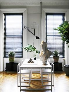 How to Create the Perfect Furniture Plan for Your Space//Modern dining area with plants and a bust, articulating sconce