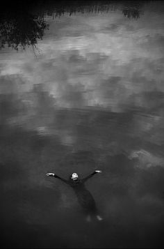 Photo by Anton k. | floating in the black lake | surrender | let it wash all over you | reflection of clouds in water | great composition | ripple effect | dark | moody | depression | black & white photography | let go | solitude | float |