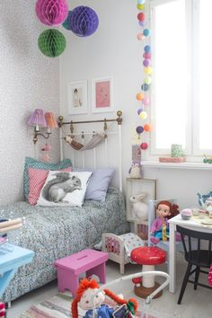 Vanha rautasänky, Tapettitalon Kirsikkapuu-tapetti ja pienen tytön pinkit lelut muodostavat iloisen kokonaisuuden. Katso kuva ja poimi parhaat ideat kotiisi!
