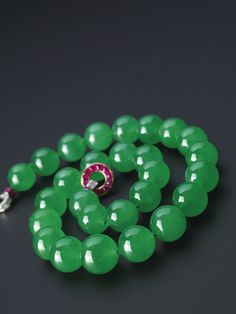 A highly important jadeite bead, ruby and diamond necklace, Cartier, Circa 1933.   Composed of twenty-seven graduated jadeite beads of highly translucent bright emerald green colour, completed by a clasp set with calibré-cut rubies and baguette diamonds, mounted in platinum and 18 karat yellow gold, length approximately 530mm, unsigned. Beads approximately 19.20 to 15.40mm.  Provenance: Formerly in the collection of Barbara Hutton, Louise Van Allen and the Princess Nina Mdivani.