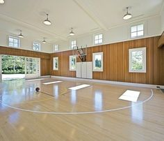A light-filled basketball gym features eastern white maple floor, custom sliding barn doors by Real Carriage Door Company and pendant lights by Barn Light Electric.
