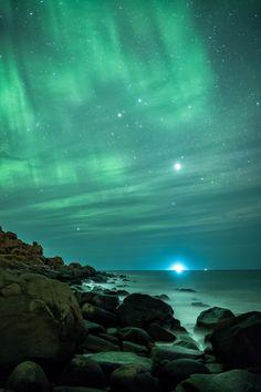 Rocks at Uttakleiv Beach an Aurora rain started to turn the sky in a green curtain.