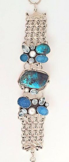 Stunning 925 Sterling Silver bracelet with Turquoise focal stone and Druzy, faceted Blue Topaz and Pearl accents. Intricately woven links and adjustable clasp with Iolite gemstone detailing.