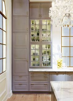 YES...this IS IKEA. Gray IKEA kitchen cabinets, glass doors, white marble counters, chandeliers.