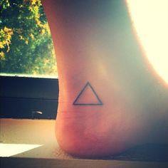 Pequeño tatuaje de un triángulo que, en términos científicos, representa el cambio, situado en el tobillo de Jay. - Pequeños Tatuajes