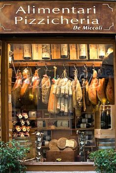 smoked meat in shop window . siena tuscany italy . masterfile.com