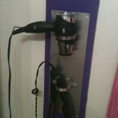 Hair dryer holder.  Made with wood, duct tape, sheet of metal, pvc pipe holders, and screws.  All supplies from Home Dept and Lowes