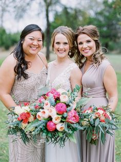 A bride stands close to her two bridesmaids as they hold their bouquets and smile at the camera at Kindred Oaks wedding venue // Jen Dillender Photography