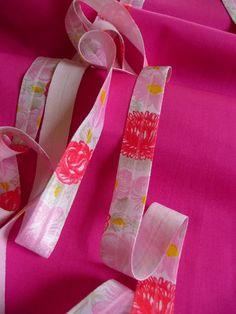 Sehr schönes elastisches Schrägband. Auf dem elastischen Schrägband befinden sich Blumen. Die Farben sind weiß, rosa, rot, gelb und grau. Die Farben sind freundliche aber dennoch nicht aufdringlich. Das Schrägband aus Gummi eignet sich sehr gut zum einfassen von dehnbaren Geweben. Das Schrägband ist im Ganzen 2 cm breit und mittig verläuft ein Streifen damit man sehen kann wo man den Schrägstreifen knicken muss.