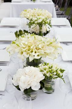 A vase full of white Calla lilies makes for a dramatic centerpiece when clustered amongst other green and white blooms.