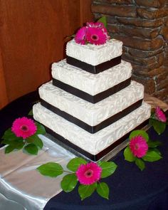 Ivory Buttercream Scolls and Dramatic Black Ribbon, accentuated with Vibrant and Bright Gerber Daisies in a Four Tiered Stacked Design Make This Cake a Classic Beauty!