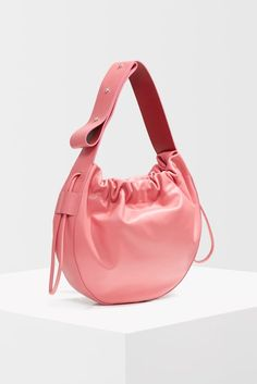 524eab867448 Add a dash of pink in to your bag collection with this drawstring bag.  Leather