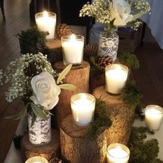 Our multi-log centrepieces with moss, fir cones, tea lights, roses and gypsophila.  Available to hire for £25.00 - perfect rustic wedding centrepiece.