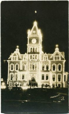 Front view of Calgary City Hall illuminated with lights at night.  Photo taken 1912.