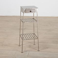 This side table features two fixed shelves and a drawer. This beautiful piece is finished in mirror nickel.