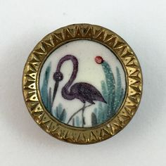 19th C. A black bird is featured on this hand painted button set in a gilt metal cup. Unique triangular shapes border.