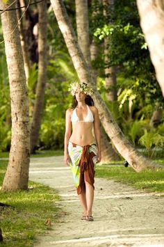 Wahine walking through a coconut grove.