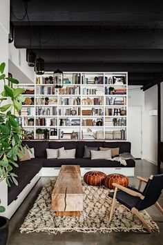 Love this corner sofa with drawers underneath and display shelving filled with all sorts of oddities behind.