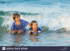 Two children playing in the sea Stock Photo