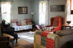 cozy farmhouse living room with wood stove, daybed, and lots of vintage and antique goodness