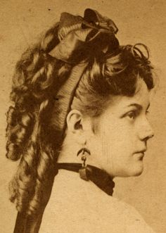Corkscrew ringlets with over-sized bow (1870s)