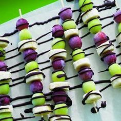 Frozen grape and banana skewers with chocolate drizzled.