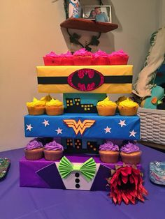 """Superhero cupcake stand inspired by Wonder Woman, Batgirl & Joker. I used colored tissue paper to wrap different sized boxes.  All the decorations are made using assorted card stock.  Joker: I found an online tutorial for making Joker's bow tie out of card stock. Used glitter card stock for his lapels. Super easy. Used actual buttons for his button and took the sunflower from an old silk flower arrangement that I had laying around the house.  Wonder Woman: her """"WW"""" was free-handed. Found an…"""