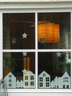 Paper cutouts of houses, trees, stars for winter window decorations
