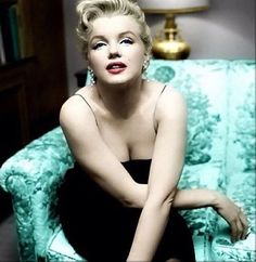 Marilyn Monroe with her hair up in a black dress sitting on the edge of a green chair.