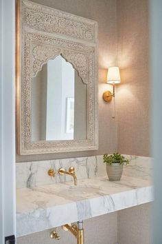 Stunning bathroom design featuring a Moroccan style carved wood vanity mirror lit by Camille Long Sconces on a grasscloth wallpaper wall. #moroccandecor #moroccan #decor #bathroom