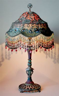 Antique metal lamp base holds a colorful Balinese shade in colors of pink, aqua and blue. Shade is covered in vintage silver Indian sari appliqués and 1920s era netting and floral trim. Colorful hand beaded fringe adorns the bottom of the shade.