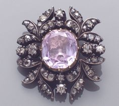 A Georgian pink topaz, diamond and silver-topped gold brooch centering an oval-shaped pink topaz, set in horizontal fashion, framed by stylized leaf motifs set with old mine-cut diamonds