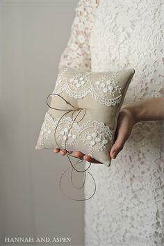 Mia es una almohada de anillo perfecto para una boda rústica. El 7 x 7 cuadrados almohada está hecha de tela de lino natural que parece arpillera de patatas de Idaho. Una capa de encaje con rosas ivory y dobladillo hilo para atar los anillos para completar el look de este portador del anillo.  Algunos información adicional sobre esta almohada: -DIMENSIÓN: 7 L x 7  W x 2.5 H -Materiales: COLOR NATURAL tejido de lino para el hilo de encaje, relleno de fibra y el dobladillo de almohada, marfil…