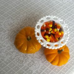 Planning an October wedding? Fill milk glass candy dishes with Halloween themed candy and pair with mini pumpkins for a unique autumn themed centerpiece!