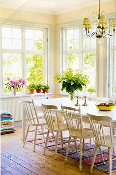 charm-filled dining room -- love the white ladder-back chairs w/matching white table // colorful striped rug // windows // pine floors
