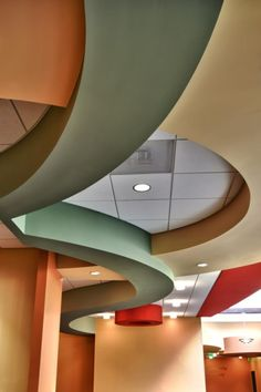 The details of the soffits, especially at the pediatric desk, show the colors of the desert and add a playful and warm quality to the department. Photographer: Dustin Revella