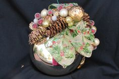 Gold shinny ornament decorated with gold berries, gold leaves pine cones, gold ribbon printed with holly leaves and berries