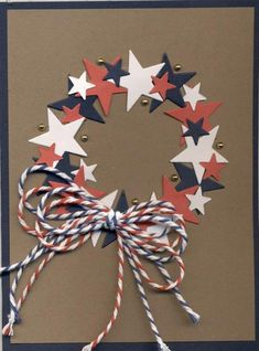 handmade card: Starry Wreath by scootsv ... red, white and blue punched/die cut stars form a wreath ... multi-loop bow of baker's twine in red white and blue stripes ... like the little gold pearls in the wreath ... kraft base card ... great patriotic card