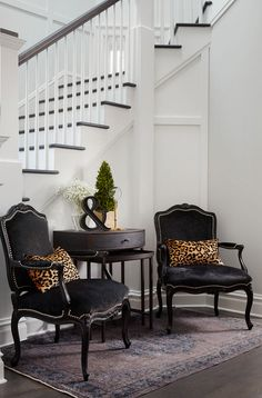 SuzAnn Kletzien - Chic foyer features a pair of black velvet French chairs…