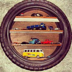 Nicho com pneu e ripas de madeira. | Além de serem super resistentes, os pneus também ganham várias funções dentro da casa. Eles podem ser usados como cuba da pia, revisteiro, prateleira para guardar brinquedos, como apoio para bancos e mesas e até como vasos para plantas. Por isso, na hora de aposentar o pneu do seu carro, inspire-se nessas dicas para sua reutilização!