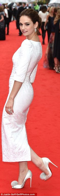 A bit of all white: Lily James wore a fitted white dress and fun heels with pom poms on th...