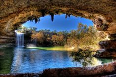 Hamilton Pool Preserve is a natural pool created when the dome of an underground river collapsed 1000's of years ago. Located about 23 miles west of Austin, Texas off Hwy 71. Hamilton Pool Preserve consists of 232 acres of protected natural habitat featuring a jade green pool into which a 50-foot waterfall flows. Surrounded by huge slabs of limestone that rest by the water's edge; large stalagtites grow from the ceiling high above. Home to the endangered golden-cheeked warbler.