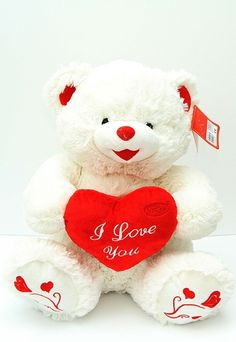 Ursulet alb, din plus, cu pernuta rosie I love you si inimioare imprimate pe labute. Inaltime: 40 cm. Produs in Romania. Cadou: 1 fir de trandafir rosu, 60 cm.