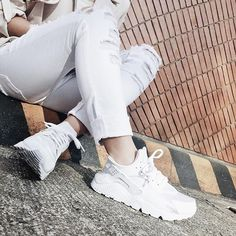 white pair of shoes,white ripped pants,brown wall,gutter