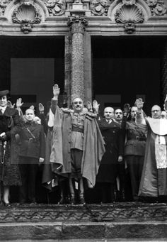 Spain - 1938. - GC - SANTIAGO DE COMPOSTELA (LA CORUÑA), 05/12/1938.- El general Francisco Franco, acompañado de su esposa, Carmen Polo y numerosas autoridades, saluda brazo en alto mientras escucha el himno de falange a la salida de la Catedral de Santiago de Compostela, donde acudió para ganar el Jubileo. Entre otros asisten: El gobernador civil, Julio Muñoz Aguilar (2º dcha), y los ministros del Interior, Ramón Serrano Súñer (4º dcha) y Agricultura Raimundo Fernández-Cuesta