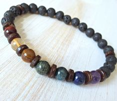 Mens tribal style seven chakras bracelet, made with High quality 8mm stones, each representing one of the seven chakras, Red Tiger eye, Baltic, Citrine, Golden Tiger eye, Serpentine, Apatite, Lapis Lazuli, dark Amethyst with Matte Volcany Lava and Coconut wood spacer beads...Strung on strong elastic cord. Check out my other Mens Unisex Bracelets here: http://www.etsy.com/shop/LifeForceEnergy?section_id=11052607 This design is Copyright by Life Force Energy shop © 20...