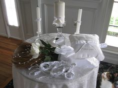 "I enjoy working with brides on a budget!  All these items are available for loan for your ceremony.  Round table with white tablecloth to be used as an altar.  Crystal Unity candlesticks.  Ring bearer pillow cross-stitched in silver ""With this ring...I thee wed.""  Decorated broom for jumping the broom ceremony. And a white handfasting cord for handfasting ceremonies."