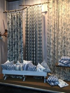 Use drapes and furniture to sell home goods at a craft fair. Display shows how pillows can work with different patterns.