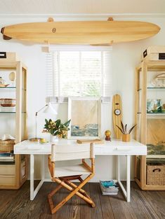 Wooden surfboards add a vintage vibe and are easy to pair with virtually anything. We love how this little office nook carries the light wood hue from the shelves to the director's chair. Surfboard Decor, Surf Decor, Surf House, Beach Room Decor, Beach House Decor, Beach Apartment Decor, Beach Chic Decor, Tropical Bedroom Decor, Beachy Room