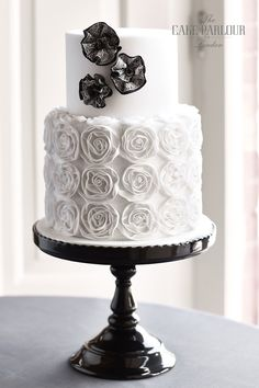 'RIBBON ROSES AND ROSETTES' Wedding Cake - Ribbon lace covering a netted base and decorated with lace layered rosettes.